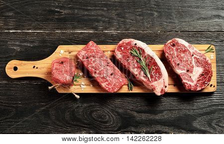 Fresh raw Prime Black Angus beef steaks on wooden board: Tenderloin Denver Cut Striploin Rib Eye