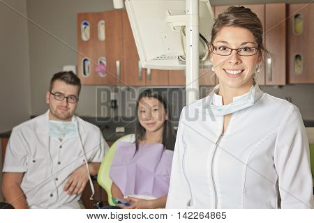 A dental office with employee and client. the dental assistant is on the front.