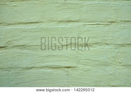 Bright, light green color, with stains on a brush on the old wall.