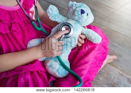 Child playing doctor or nurse with plush toy bear at home. Happy girl listens a stethoscope to toy. Playful girl role playing.