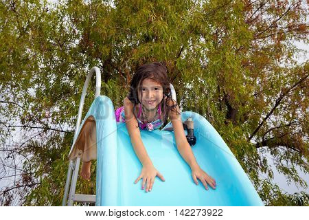 A little girl lays on top of a pool slide and is about to slide down on her tummy. She smiles and has a hose next to her to wet the slide down.