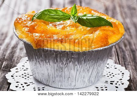 French cuisine- julienne. Mushroom chicken and cheese gratin in Aluminum Foil Mini Baking mold decorated with basil leaves on openwork napkin authentic recipeclose-up