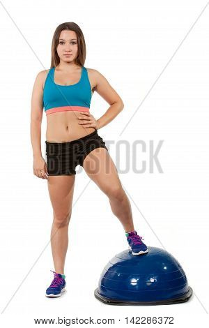 Young sports girl does exercises on spotrivnom simulator bosu. Portrait in full growth. He looks into the camera.