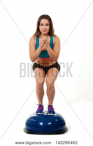 Young sports girl does exercises squatting on spotrivnom simulator bosu. Portrait in full growth. He looks into the camera.