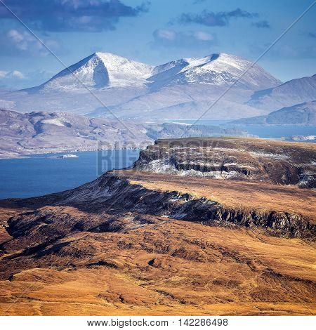 The snowy Scottish Highlands skyline shot from the Old Man of Storr at daytime - Isle of Skye, Scotland, UK