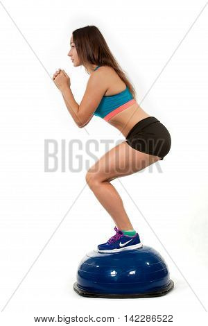 Young sports girl does exercises squatting on spotrivnom simulator bosu. Portrait in full growth. View profile.