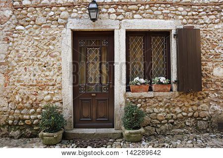 Stained-glass window and door of old stone house at medieval village Perouges in France