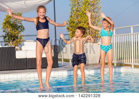 happy children playing near the swimming pool at the day time. Concept of friendly family.
