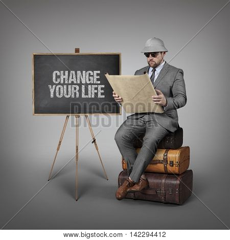 Change your life text on  blackboard with explorer businessman sitting on suitcases