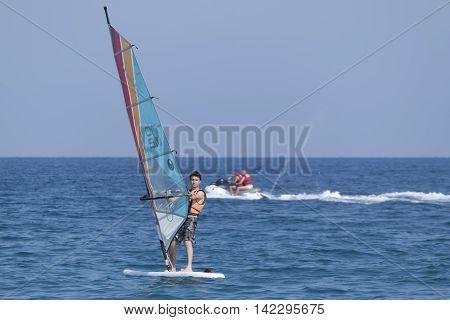 Unidentified Turkish Man Glides Over The Waves Of The Mediterranean Sea Windsurfing