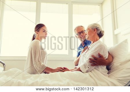 medicine, support, family health care and people concept - senior man and young woman visiting and cheering her ill grandmother at hospital ward