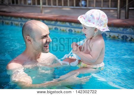 Father and daughter are swimming in a pool