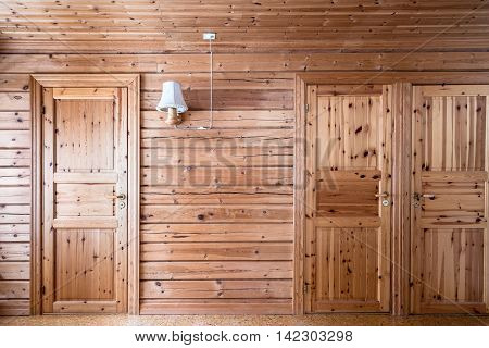 Sparse pinewood interior wall with two pinewood doors and a wall lamp in Scandinavian cabin.