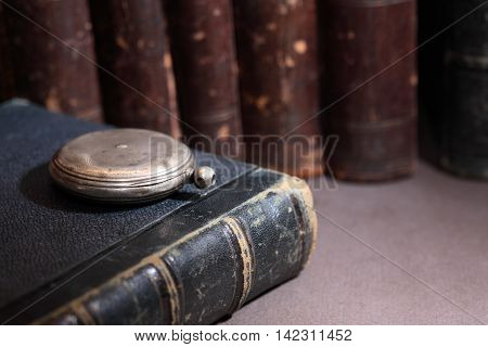 Vintage library. Old silver pocket watch near book in a row on dark background