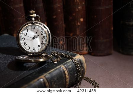 Vintage library. Vintage pocket watch near book in a row on dark background