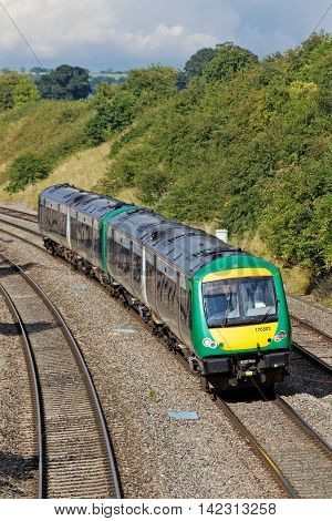 STOKE POUND, UK - AUGUST 4: A local London Midland commuter service heads toward the suburbs of Birmingham on August 4, 2014 in Stoke Pound. London Midland call at 146 stations operating over 868Km