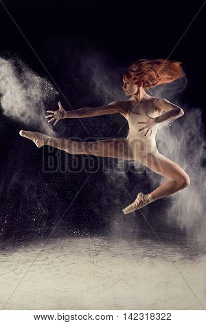 Dancer high jump and the explosion of white dust. Dramatic portrait of strong woman dancer with white powder on black background.