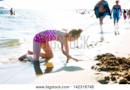 CORFU, GREECE - JULY 28, 2016: Little girl playing with sandcastle at the sea front against of sun reflection. Greece