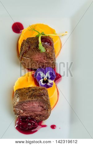 Beef fillet mignon grilled and garnished meat with colorful vegetables red berry sauce decorated with flower on white background