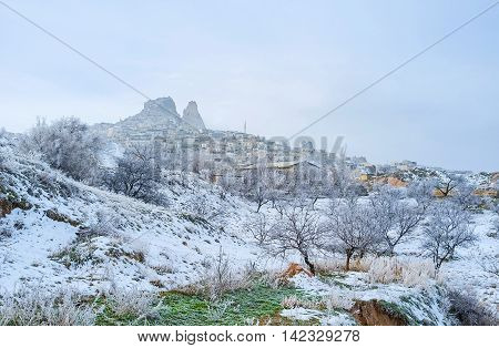 The snowy valley and the Uchisar historic village topped with the natural rock citadel the notable landmark of Cappadocia Turkey.