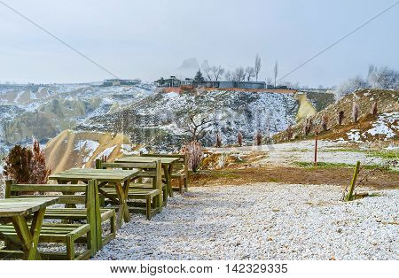 The snowy hill with empty tables next to the Pigeon Valley with the Uchisar rock in fog on the background Cappadocia Turkey.