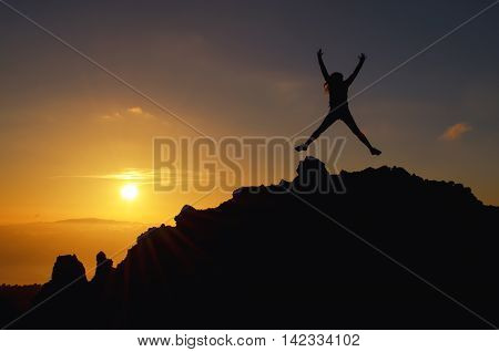 Young woman jumping at a sunset on a mountain of joy on holiday in the air