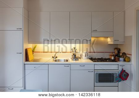 front view of a domestic kitchen, cabinets and hob