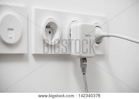 Powerline network adaper plugged into a wall socket poster