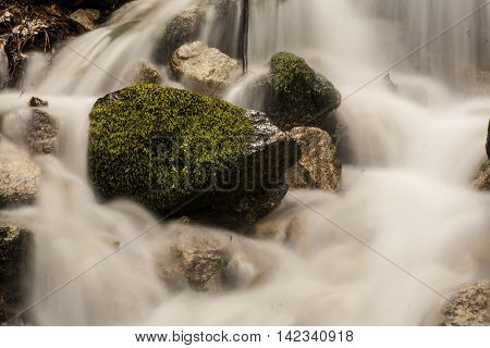Cascading water over rocks with green moss