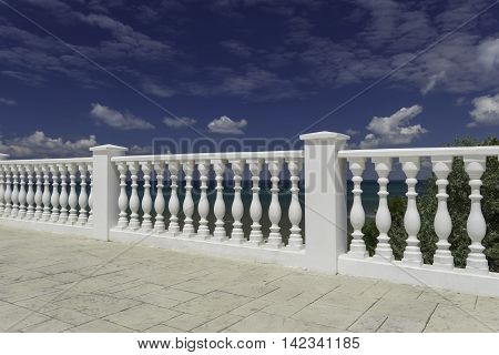 White decorative fence on the waterfront of the city of Anapa resort on the Black Sea coast. Blue cloudy sky water with an emerald hue.