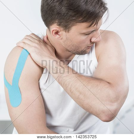 Picture of athletic man with arm pain during kinesiotherapy