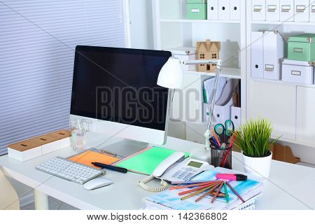 Designer working desk with computer and paperwork.