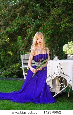Portrait of beautiful woman dressed in evening gown. Blonde Beautiful woman in long purple dress like princess sitting at a garden table in green garden. Woman holding a bouquet of wildflowers.