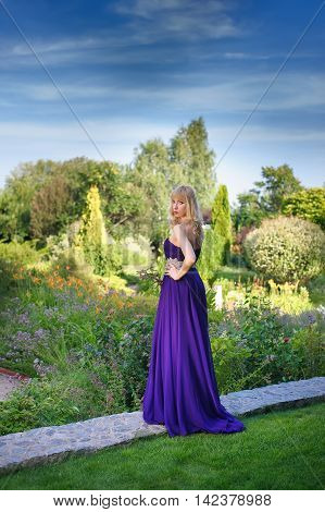 Portrait of beautiful woman dressed in evening gown. Blonde Beautiful woman in long purple dress like princess in green garden. Woman holding bouquet of wildflowers. Look at camera.