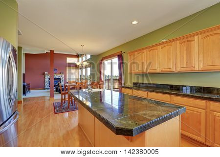 Spacious kitchen with green walls and hardwood floor. Has stainless steel appliances kitchen island maple storage combination and tile counter tops. Northwest USA poster
