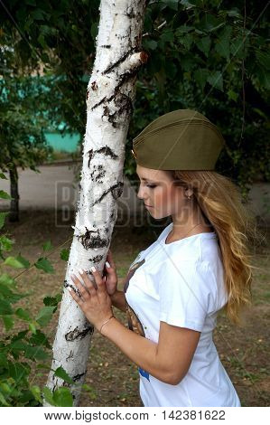 Girl in a military garrison cap and in a t-shirt about a birch