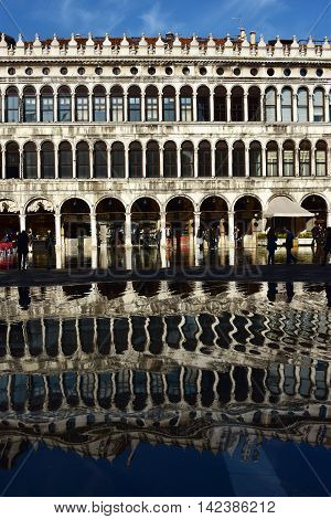 VENICE, ITALY - NOVEMBER 28: Reflection of Procuratie Vecchie in Saint Mark Square during 'Acqua Alta' (venetian high tide) NOVEMBER 28, 2015 in Venice, Italy