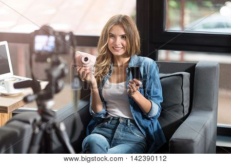Modern blogger. Cheerful delighted smiling woman sitting on the couch and feeling content while shooting a video