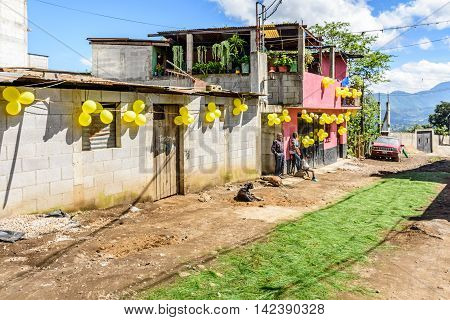 San Juan del Obispo Guatemala - June 26 2016: Houses adorned with balloons & pine needle carpet in street as part of St John's Day celebrations in village named after the patron saint. Near Antigua, a UNESCO World Heritage Site.