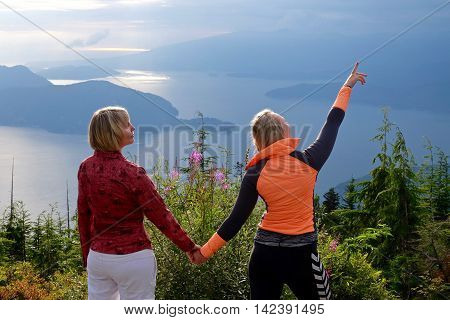 Mother and daughter holding hands outdoor. Bowen Lookout in Cypress Mountain Provincial Park North Vancouver British Columbia Canada.