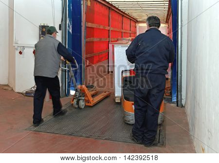 Two Workers Loading Goods in Truck With Pallet Jack