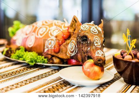 Decorated and roast suckling pig with an apple in his mouth on a white plate on banquet