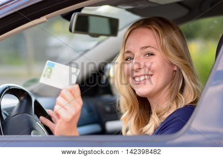 Happy young blond woman sitting behind the steering wheel of a car showing off her drivers license through the open window