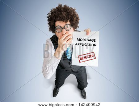 Disappointed Businessman Is Showing Paper With Denied Mortgage A