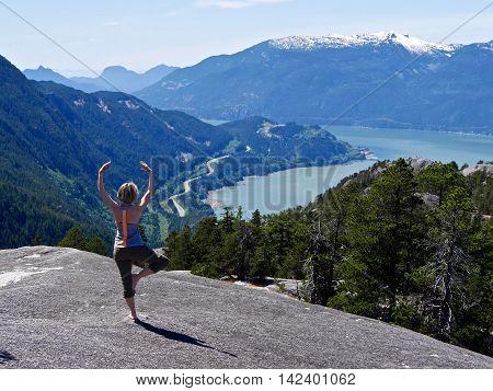 Woman exercising at mountain top. Stawamus Chief Summit Garibaldi Provincial Park British Columbia Canada.