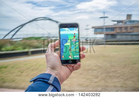 Male Hand Holding Iphone 6 With Pokemon Go In Frankston Foreshore