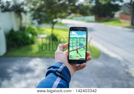 Male Hand Holding Iphone 6 With Pokemon Go In Residential Area