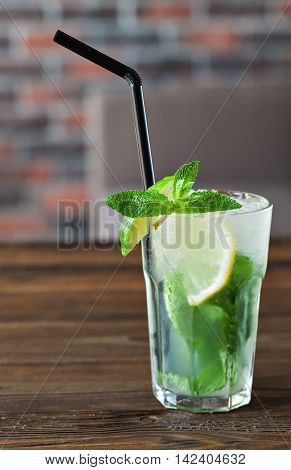Lemonade with lime, mint on a wooden table. Summer drink.