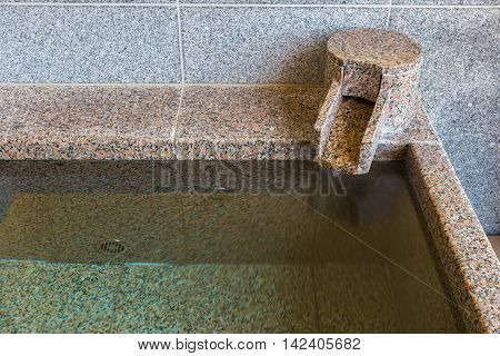 Close up section of onsen marble bathtub and marble faucet Japanese style bath
