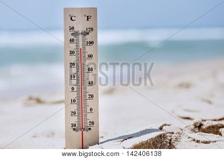 A temperature scale on a beach shows high temperatures during a heat wave. Concept photo of heat wave , warm weather, global warming, high temperatures, climate change.